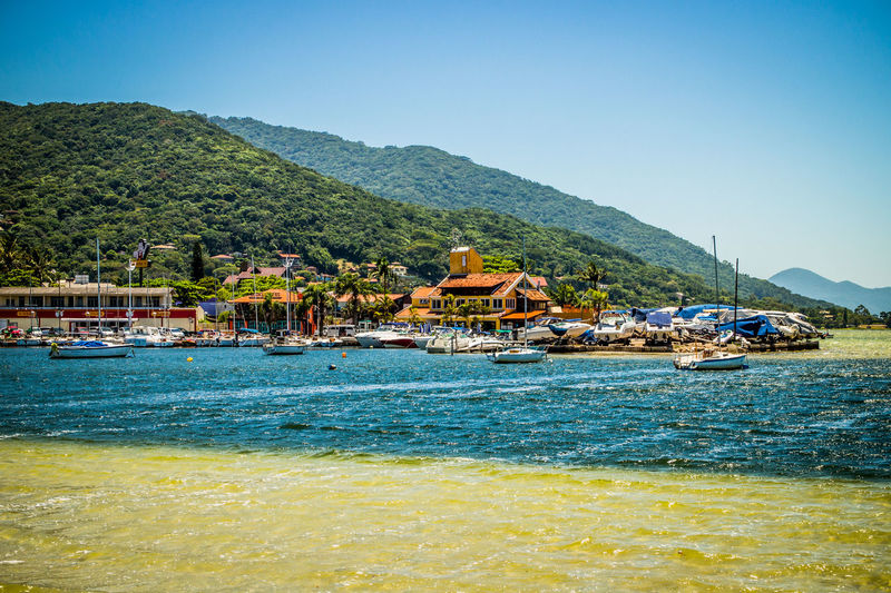 Lagoa Da Conceição Architecture Beach Beauty In Nature Blue Building Exterior Built Structure Clear Sky Day Florianópolis Brasil Mountain Mountain Range Nature Nautical Vessel No People Outdoors Scenics Sea Sky Tranquility Transportation Tree Water Waterfront