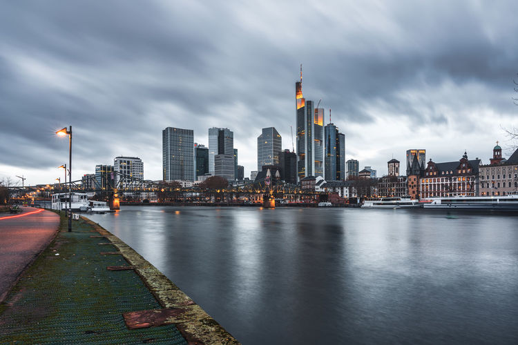 View of buildings by river against cloudy sky