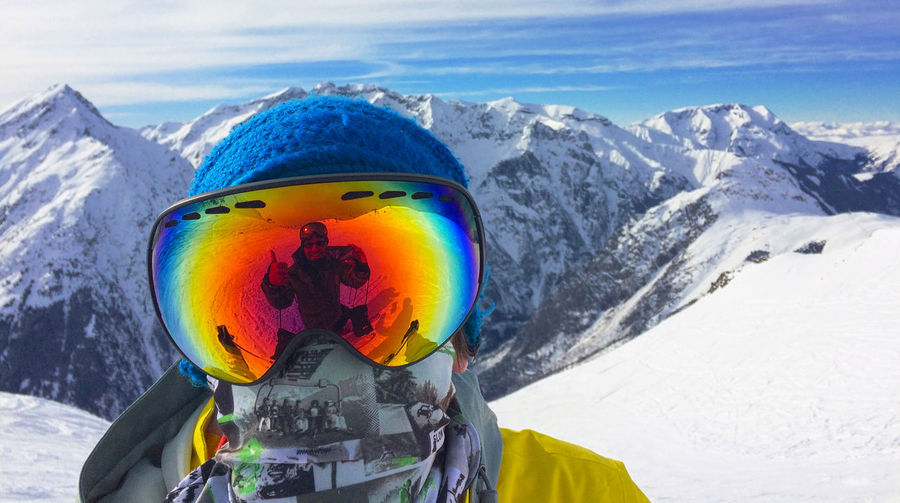 Close-up portrait of person wearing ski goggles with reflection against snowcapped mountains