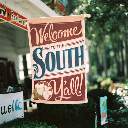 A banner welcomes customers to the South and to the Hammock Shops on Pawleys Island, South Carolina. Banner Bokeh Film Flag Focus On Foreground Greeting Hammock Shops Hasselblad Large Aperture Message Myrtle Beach No People Outdoors Pawleys Island Shopping Sign South Carolina Southern Hospitality Text The South Trees Welcome Welcome Sign Welcome To The South Western Script