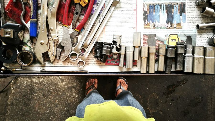 Low section of mechanic standing by tools on workbench