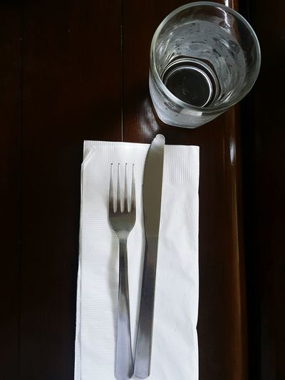 Directly above shot of eating utensils with drinking water on wooden table