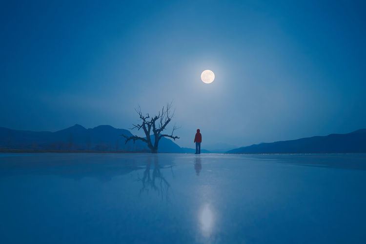 Scenic View Of Frozen Lake Against Blue Sky At Night