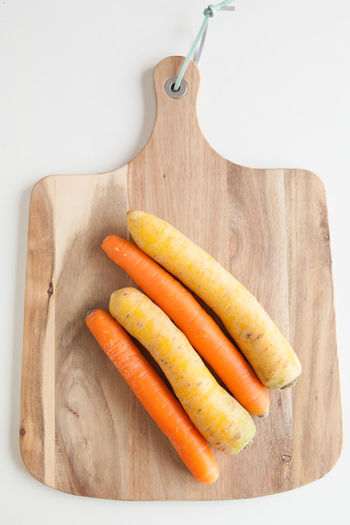 Fresh vegetables, orange and yellow carrots on a wooden cutting board against a white background top view Food And Drink Food Healthy Eating Still Life Indoors  Freshness Carrot Root Vegetable Vegetable High Angle View Directly Above Wellbeing Wood - Material Cutting Board Close-up Table Orange Color No People Group Of Objects Studio Shot