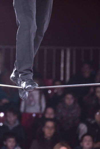 Low section of performer walking on tightrope during event