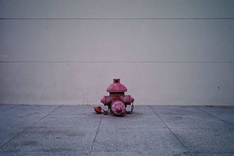 Fire hydrant on footpath against wall