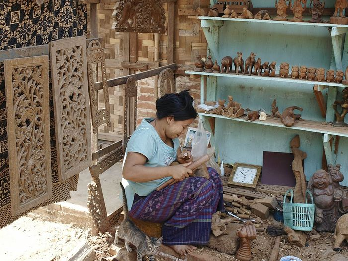 Woman craving wood while sitting at market