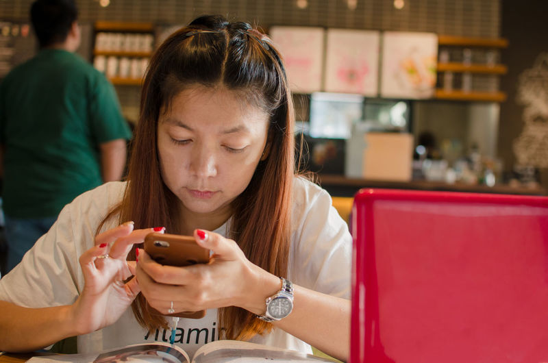 Close-up of woman using smart phone at table in cafe