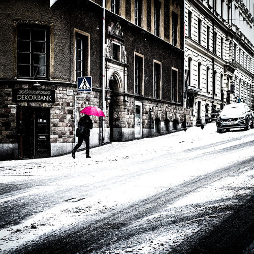 Rear view of person walking on snow covered city