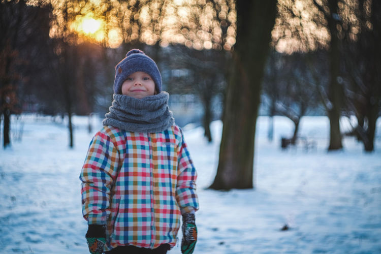 Portrait of smiling boy standing in snow