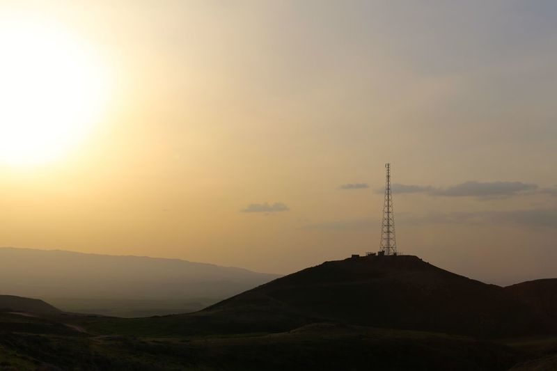 Communications tower on top of silhouette mountain during sunset