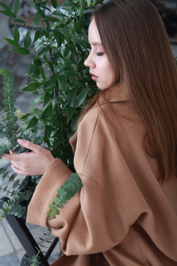 Beautiful woman with plants against wall