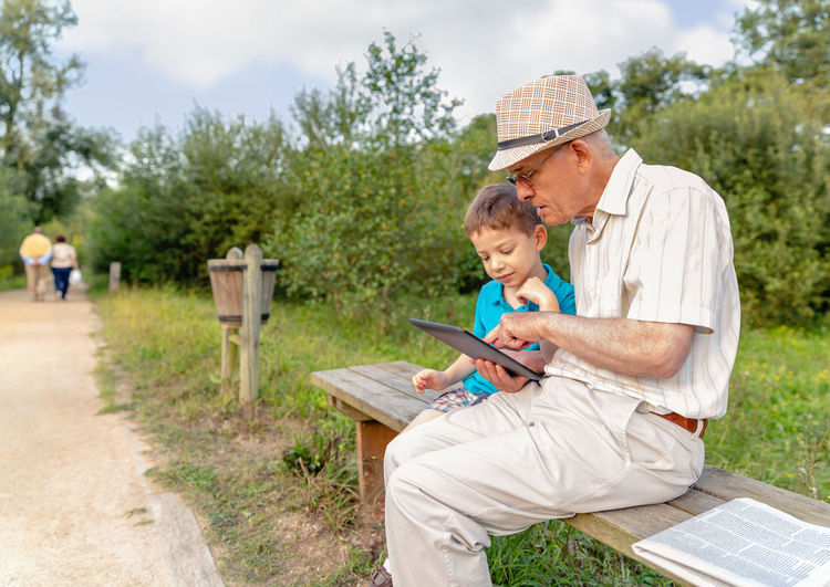 Grandchild teaching to his grandfather to use a electronic tablet on a park bench. Generation values concept. Caucasian Age Hat Parent Real Communication TAB Touchscreen Complicity Reading Together Education Internet Sitting Male Adult Background Man Kid Child People Happy Boy Touchpad Technology Pad Leisure Lifestyle Old Two Elderly Outdoors Bench Seat Park Nature Family Generation Using Learning Learn Teaching Teach Electronic Tablet Senior Grandparent Grandfather Grandchild Grandson