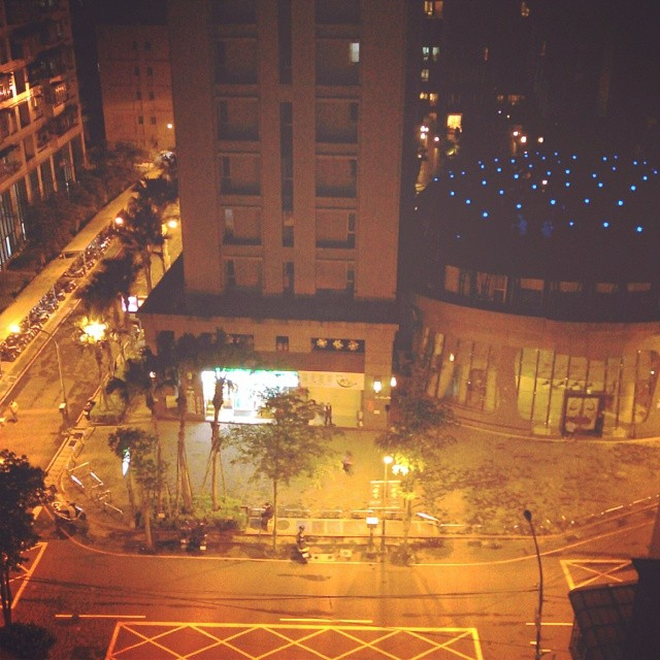 illuminated, night, building exterior, architecture, built structure, city, street, street light, high angle view, lighting equipment, sidewalk, outdoors, residential building, building, city life, reflection, tree, no people, road, city street