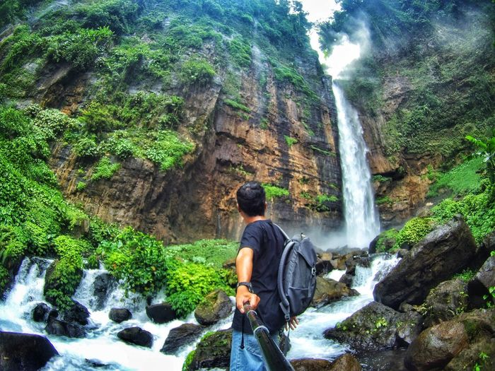 Man holding with monopod standing in front of majestic waterfall