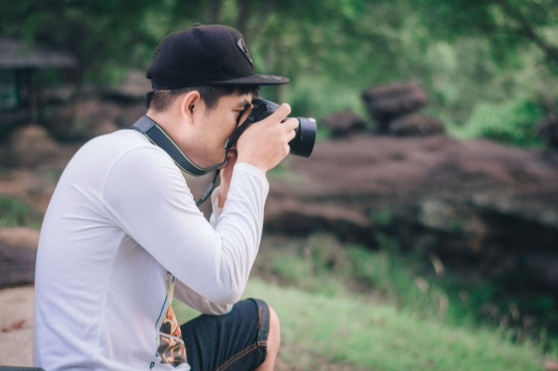 Side view of young man photographing with camera in forest