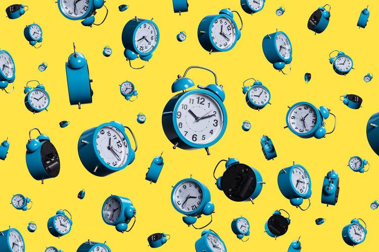 Full frame shot of alarm clocks on yellow background