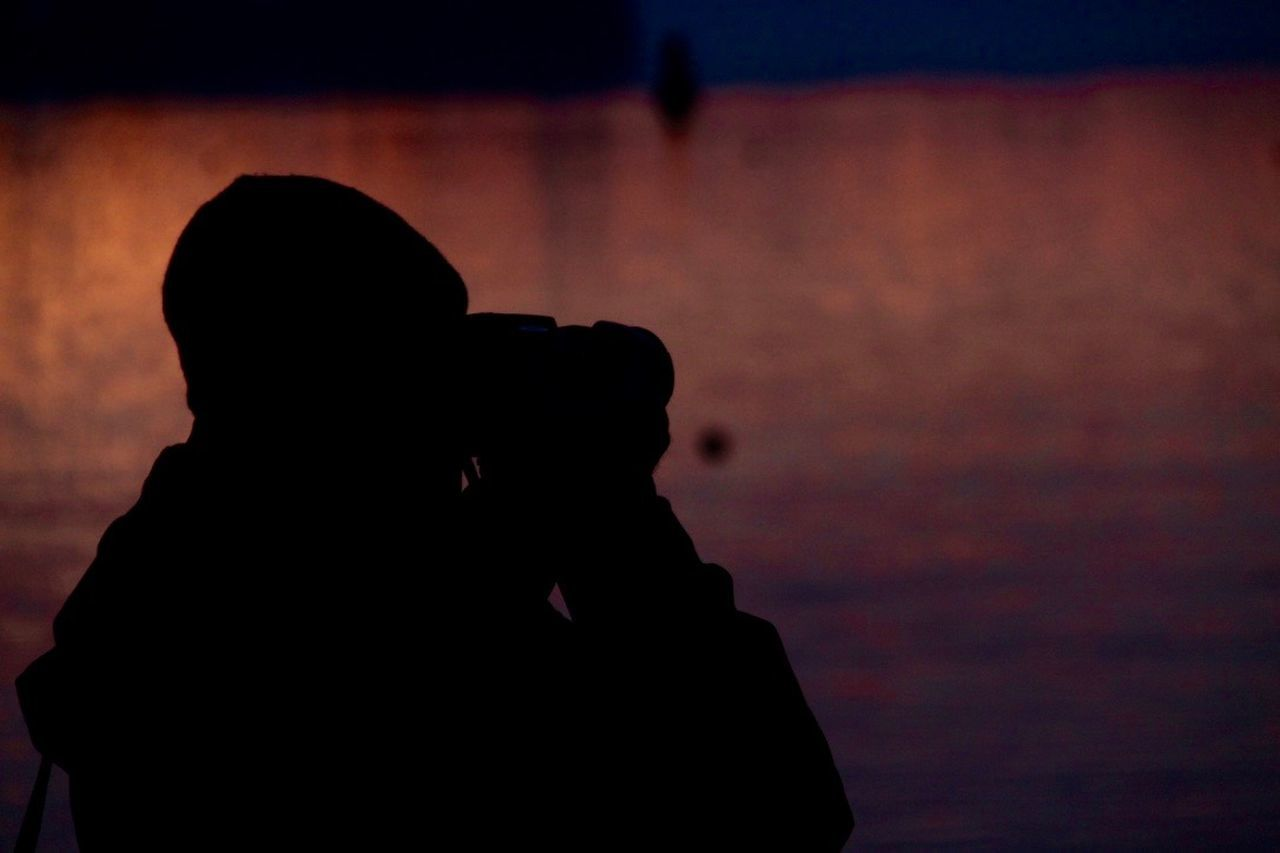 silhouette, photography themes, photographing, real people, camera - photographic equipment, leisure activity, water, sunset, nature, technology, photographer, lifestyles, holding, outdoors, one person, men, beauty in nature, women, digital single-lens reflex camera, close-up, sky, day, people