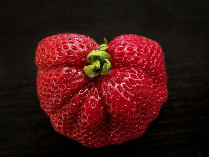 Close-up of strawberry on table against black background