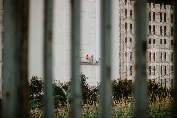Building seen through metal fence