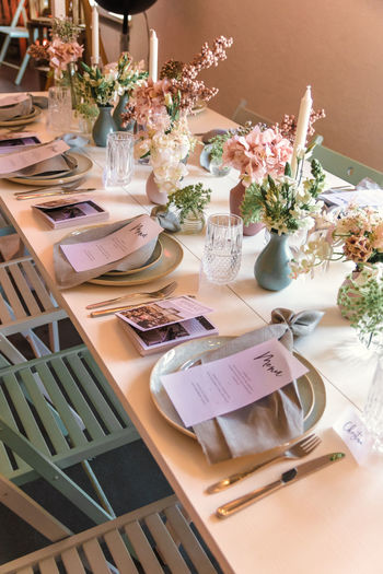 Table Flowering Plant Plant Flower Setting Indoors  No People Place Setting Vase Food And Drink Furniture Arrangement Plate Dining Table Business High Angle View Restaurant Eating Utensil Kitchen Utensil Household Equipment Glass Crockery Place Mat Flower Arrangement