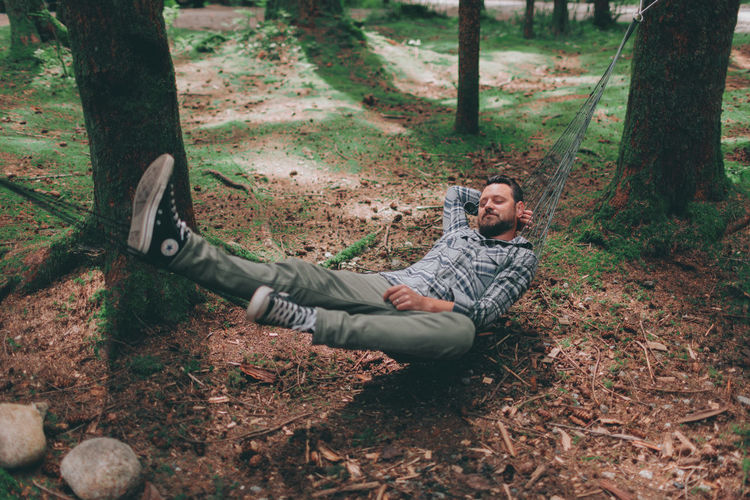 A man relaxing in a hammock in the forest. Forest Lying Down Leisure Activity Relaxation Outdoors Hammock Relaxing Man Camping