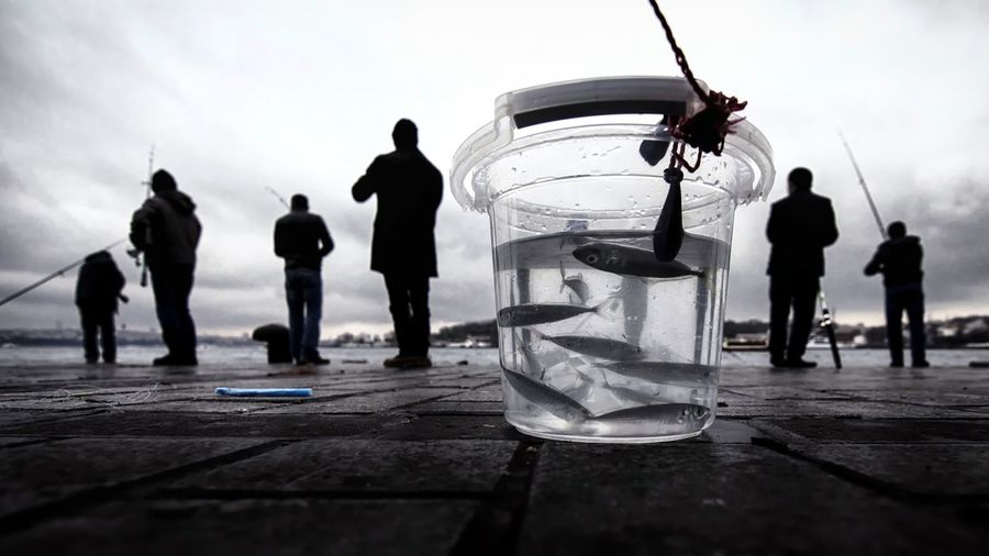 Close-up of fish in jar with people in background at lake