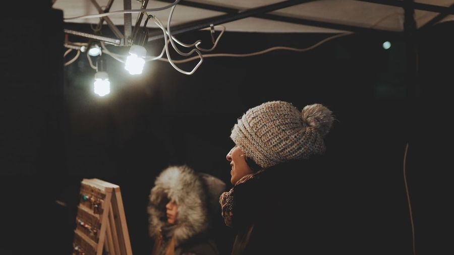 Street Photography EyeEm Selects Illuminated Real People Women Adult Rear View Warm Clothing Clothing Night Winter One Person Headshot Focus On Foreground Lighting Equipment Lifestyles Hat Knit Hat Hairstyle Portrait Electric Light Cold Live Event