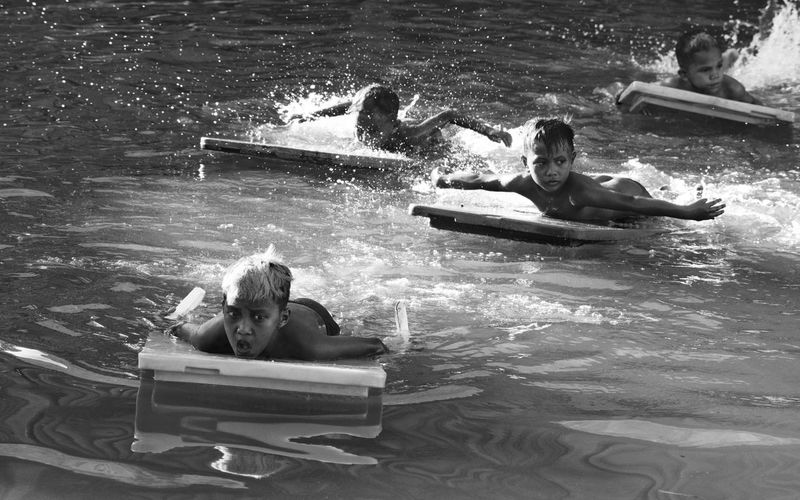 Children Swimming Through Wood On Lake