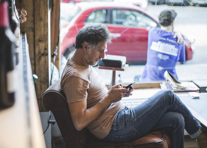 Rear view of man using mobile phone while sitting in bus