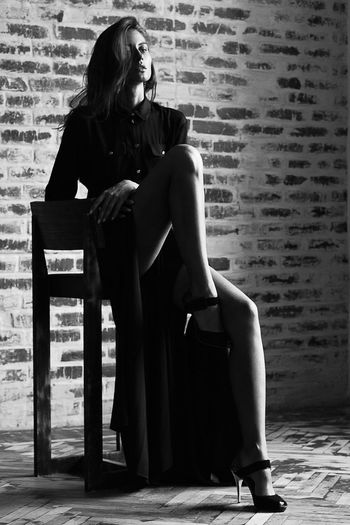 Full length of confident beautiful woman with hand on chin sitting on chair against brick wall