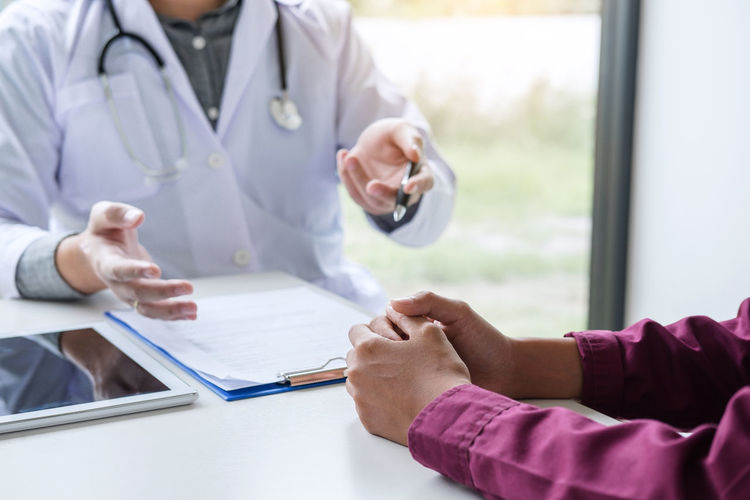 Midsection Of Doctor And Patient Discussing On Table At Hospital