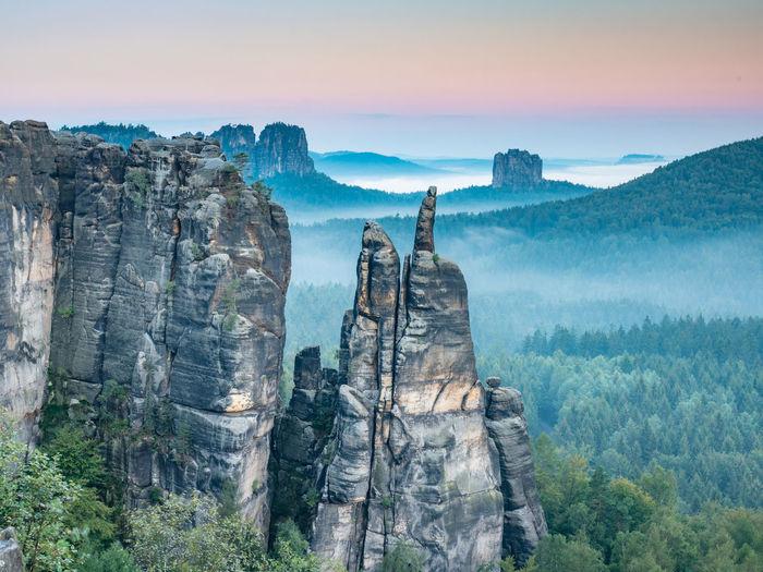 Jagged rocks near blossstock and affensteine, falkenstein massif in the valley of the evening fog.