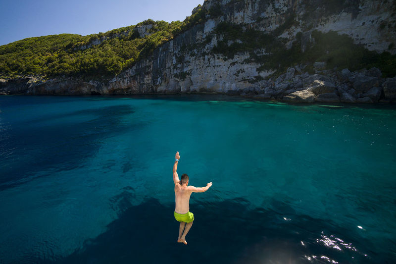 Rear view of shirtless man jumping in sea