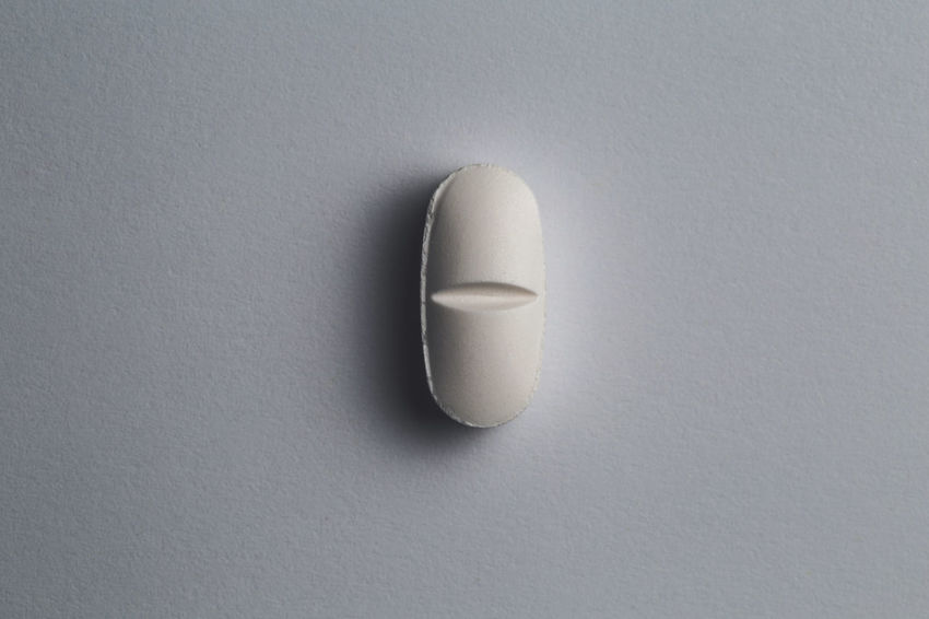 close up of a pill in isolated background Indoors  Copy Space Pill Dose Studio Shot Medicine No People Close-up White Background Healthcare And Medicine White Color Still Life Capsule Single Object Directly Above Two Objects Prescription Medicine Shadow Table High Angle View