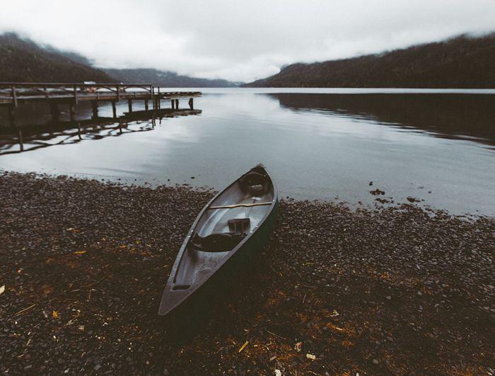 Canoe On Lakeside Against Sky