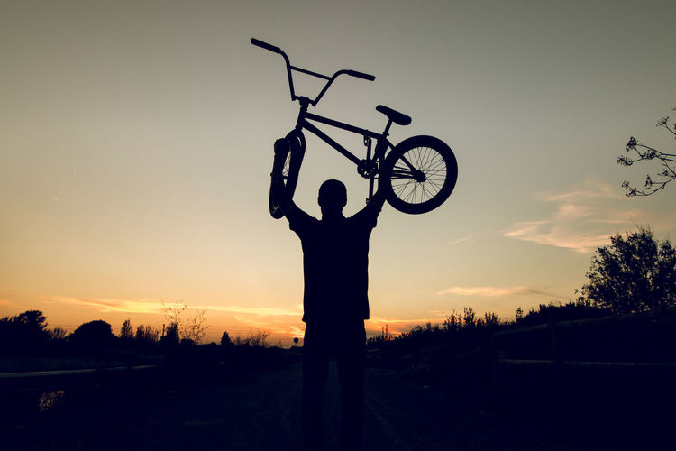 Silhouette man standing by bicycle on field against sky during sunset