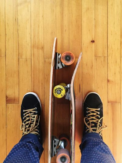 Low Section Of Man With Skateboard Standing On Hardwood Floor