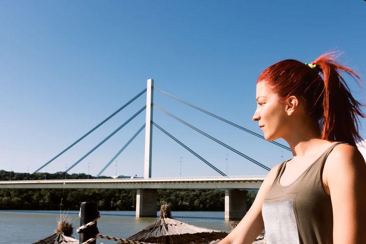 Woman looking at bridge against clear blue sky