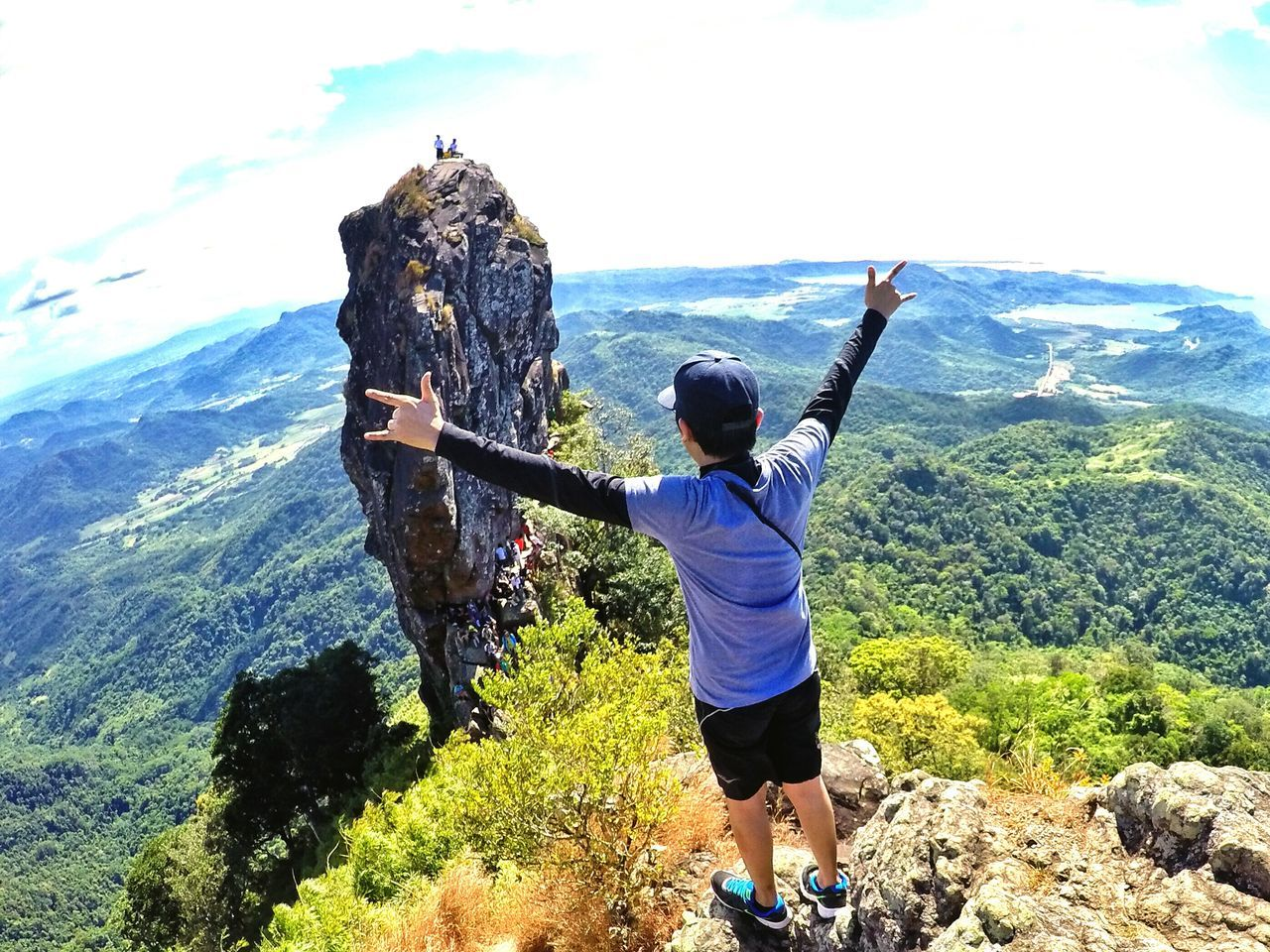 High Angle View Of Man With Arms Outstretched On Mountain Against Sky