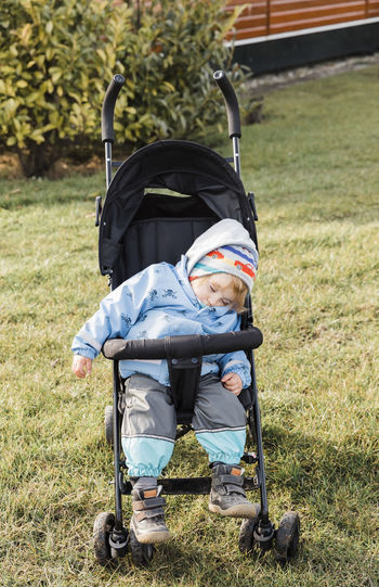 Full length of baby girl sleeping in carriage on field