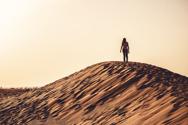 Woman Walking On Sand Dune Against Clear Sky During Sunset