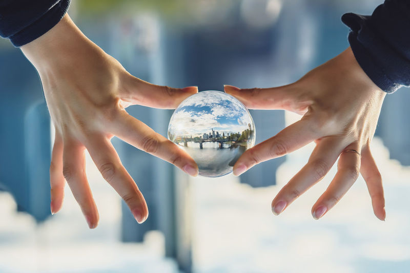 Cropped hands holding crystal ball with reflection