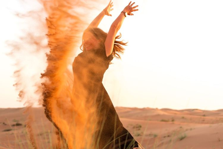 Woman Playing With Sands At Desert Against Clear Sky