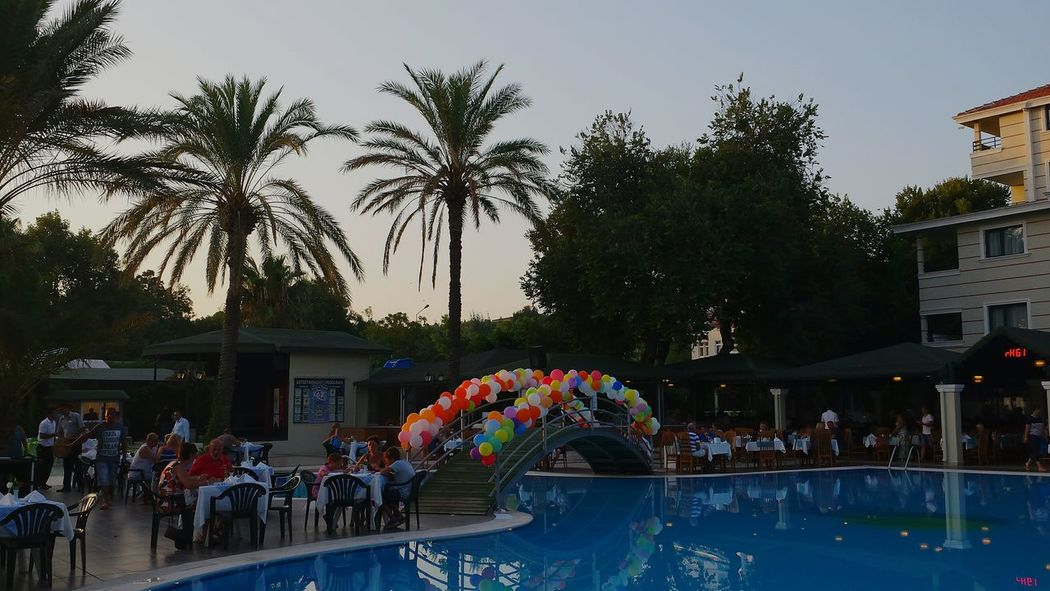 Outside Dining Poolside Hotel Sandy Beach Side Turkey After Sunset Great Atmosphere Poolside Dining Coconut Trees Water Reflections Baloons Bridge Over Little Water Bridges Bridge Many Ballons Decorated With Baloons Garden Party Palm Trees Coconut Tree Palms Palm Tree Cool Decoration Colourful Balloons Fine Dining Garden Photography Garden Design