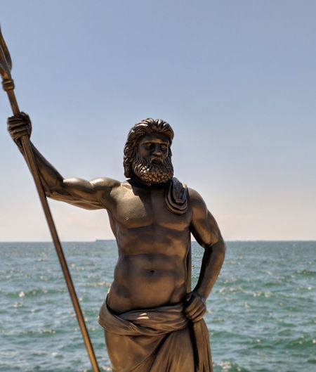 Statue by sea against clear sky