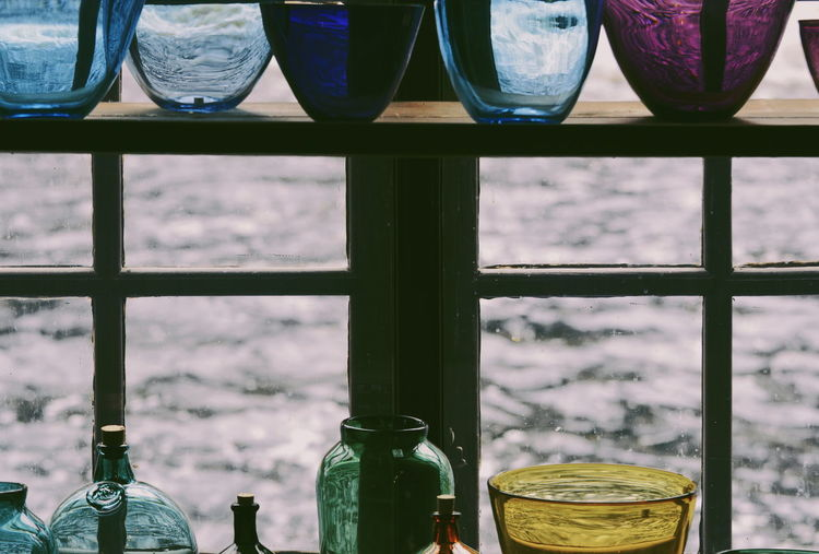 Close-up of glass bottles on window