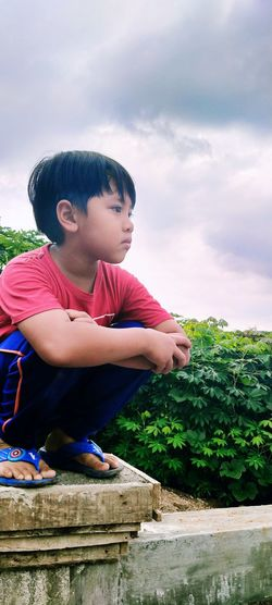 Boy looking away while sitting on land against sky