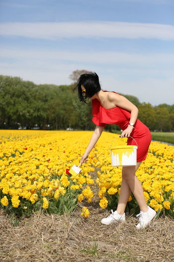 Girl with yellow flowers on field against sky