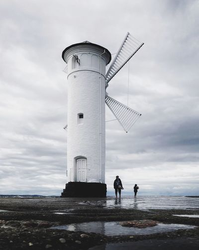Low angle view of people standing by lighthouse against sky